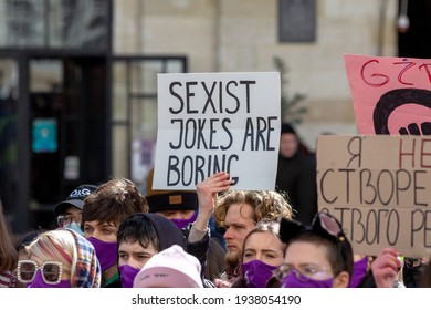 """Lviv, Ukraine - March 8, 2021: A feminist march and rally on March 8th for International Women's Day. A man holds a poster with the inscription: """"Sexist jokes are boring""""."""