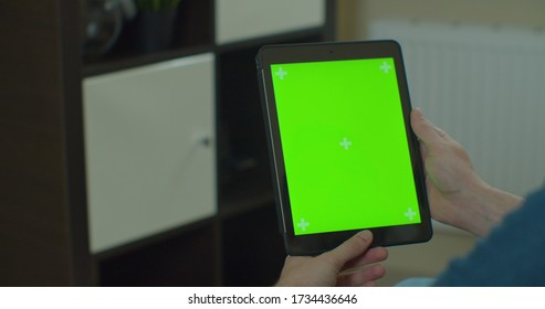 Lviv, Ukraine - May 12, 2020: Man using vertical TabletPC with green screen. Close-up shot of man's hands with Tablet. Chroma key. Close up.