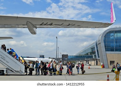 Lviv, Ukraine - May 18, 2019: Lviv, Ukraine - May 18, 2019: Boarding passengers on a plane of carrier Wizz Air near the passenger terminal of Lviv Danylo Halytskyi International Airport.