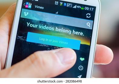 LVIV, UKRAINE - May 19, 2015: Hand holding white Samsung Smart Phone with Vimeo network Log In Screen