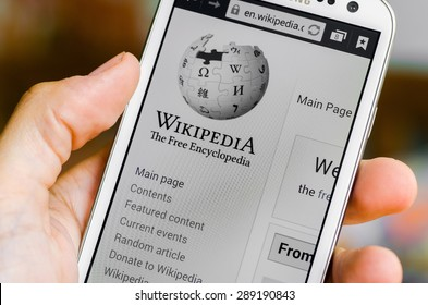 LVIV, UKRAINE - May 19, 2015: Hand holding white Samsung Smart Phone with Wikipedia main page screen