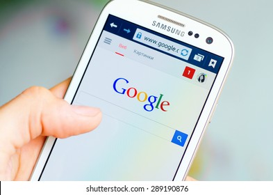 LVIV, UKRAINE - May 19, 2015: Hand holding white Samsung Smart Phone with Google search site