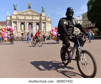 Lviv, Ukraine - May 30, 2015: A man dressed as Darth Vader on the bicycle and Lviv Opera House in the background.