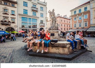 Lviv, Ukraine - May 30, 2018: Young couple making selfie on Amphitrite fountain on Market square in Lviv