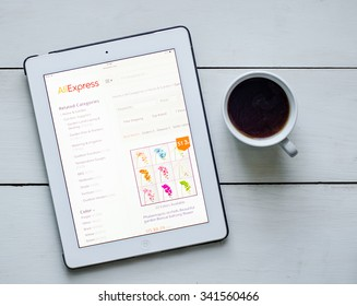 LVIV, UKRAINE - Sept 17, 2015: White ipad with AliExpress site application on screen, on white wood desk, and cup of coffee