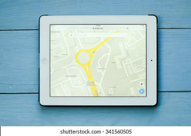 LVIV, UKRAINE - Sept 17, 2015: White ipad with Google map application on screen, on blue  wood desk