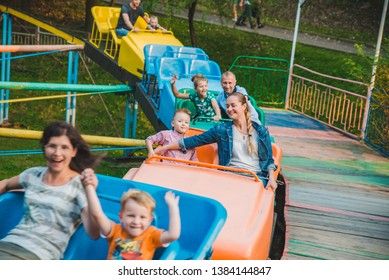 LVIV, UKRAINE - September 1, 2018: people riding attraction in city park. having fun. mother with kid.