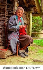 Lviv, Ukraine - September 2018: A woman knits outside a traditional Ukrainian house