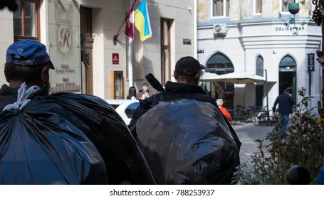 Lviv, Ukraine-September 26, 2017: Two scavengers come with large black garbage bags along the city street.