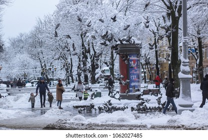 Lviv/Ukraine - 06.02.2018: Happy family is breeding birds with birdseed on holiday in snowy nature park.