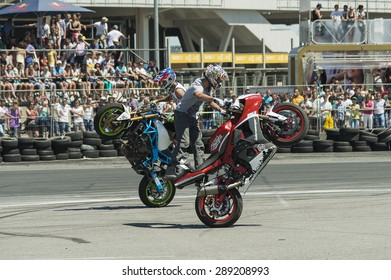 Lvov, Ukraine - June 7, 2015: Unknown stunt bikers  entertain the audience before the start of the championship of drifting near Arena - Lvov stadium in Lvov, Ukraine.