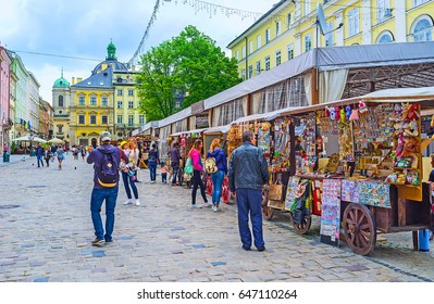LVOV, UKRAINE - MAY 16, 2017: The tourist stalls in Market Square (Ploshcha Rynok) with the historic mansions on the background, on May 16 in Lvov.