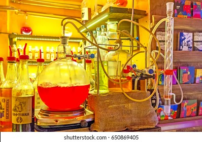 LVOV, UKRAINE - MAY 16, 2017: The simulation of alcohol producing in cafe, designed as chemical laboratory with flasks, bottles, cylinders and rubber tubes, on May 16 in Lvov.