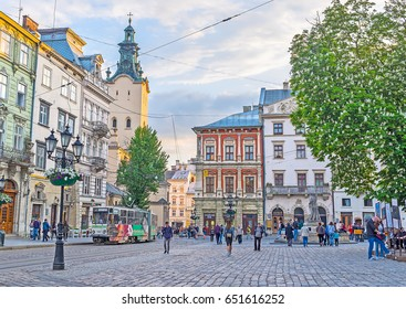 LVOV, UKRAINE - MAY 16, 2017: The tram rides along the Market Square with the bell tower of Latin Cathedral on background, on May 16 in Lvov.