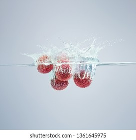 Lychee berries fall into the water scattering a lot of splashes and drops.