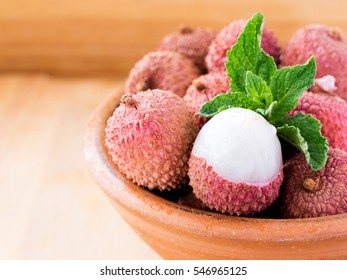 lychee fruit in clay plate on wooden background close up