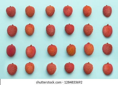 lychee fruits lie in rows on a turquoise blue background.