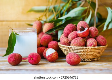 Lychee juice on wooden table / Fresh lychee drink and slice peeled with green leaves harvest in basket from tree tropical fruit summer in Thailand