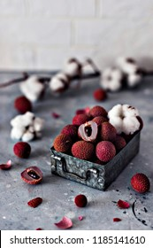 Lychee in a metal box on a concrete background with branches of cotton