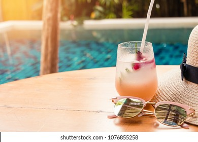 Lychee soda cocktails sunglasses and straw hat on table with blurred poolside background. Summer drinks concept.