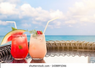 Lychee and Watermelon soda cocktails on table with blurred poolside and beach background. Summer drinks concept.