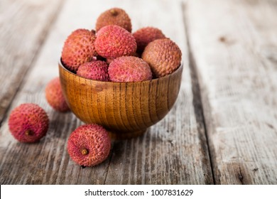 Lychee in a wooden bowl on the table. Delicious tropical fruit.