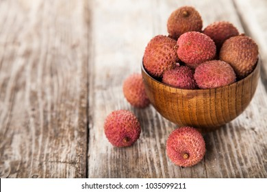 Lychee in a wooden bowl on a  table. Delicious tropical fruit.