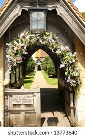 Lychgate entrance to an English Village Church with Flowers covering the Archway