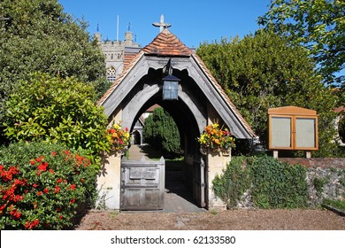 Lychgate Entrance to an English Village Church with colorful flower display and hedgerow of red berries