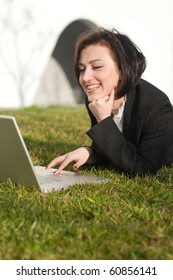 Lying brunette businesswoman with a laptop