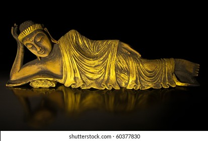 Lying Buddha statue made of teak wood on black.