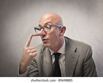 Lying businessman observing his long nose