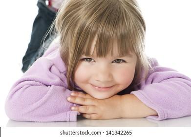 Lying little girl isolated on white