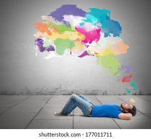 Lying man thinking creatively with colorful splash