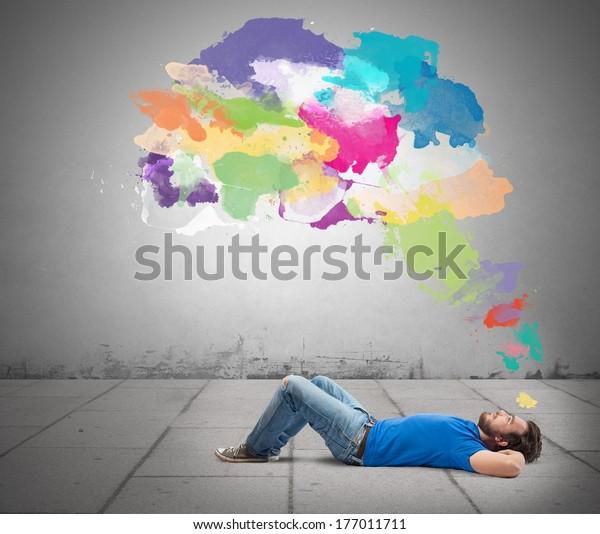 Lying man thinking creatively with colorful splash