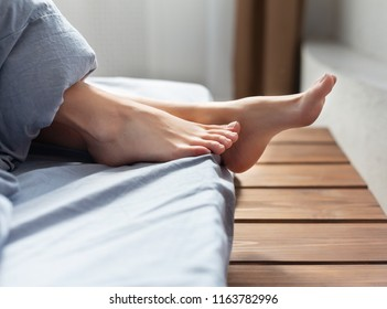 Lying on bed, female feet under blanket in bedroom