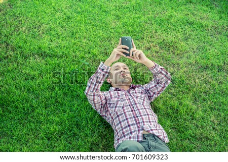 lying on grass man using smart stock photo edit now 701609323