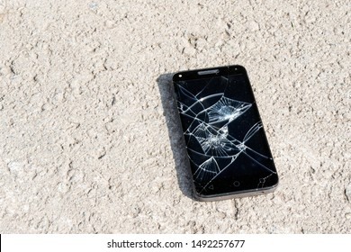 lying on the pavement among the small stones smartphone with a broken screen. lost or abandoned phone on the foyer part