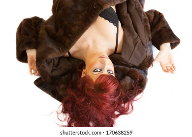 lying sensual young red-haired woman wearing underwear and mink fur coat