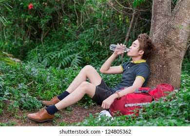 Lying tired tourist drinking water in the forest