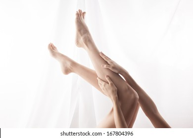 Lying woman stroking feet. high key