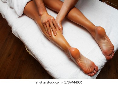 Lymphatic drainage massage of legs and lower legs. Female feet in the hands of a masseur.