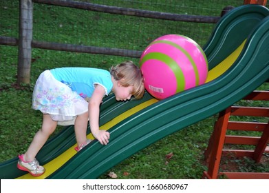 Lynchburg, Virginia / USA - July 23, 2016: A little girl inadvertently illustrating the myth of Sisyphus with her beach ball on her sliding board.