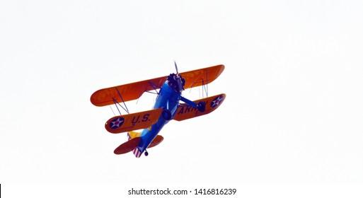 Lynchburg, Virginia / USA - June 5, 2019: A World-War-II-era Boeing-Stearman biplane trainer taking off from Lynchburg's Regional Airport.