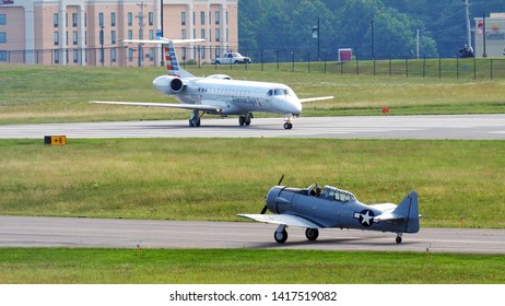 Lynchburg, Virginia / USA - June 6, 2019: A World-War-II T-6 trainer waiting to take off behind a modern American Airlines Embraer ERJ140 regional jet at the  Lynchburg Regional Airport.