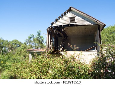 Lynchburg, Virginia / USA - September 20, 2020: An overgrown abandoned house located in suburban Lynchburg and photographed on September 20, 2020.