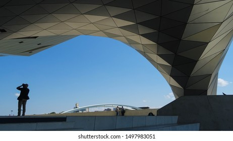 Lyon / France - 05 25 2019 : tourist man taking photo of futuristic pillar of Musée des Confluences (Confluence museum), science exhibition museum and touristic attraction in Lyon, France, Europe