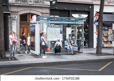 Lyon, France - August 04 2016- at a bus stop, a group of people standing or seated await the passage of the bus in Lyon in 2016 showing diversity of the inabitants of the city