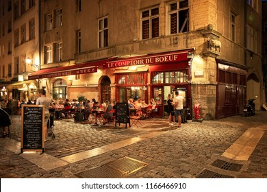 LYON, FRANCE - August 21, 2018: Colorful saint Jean district in old Lyon, the famous old town of the city of Lyon by night. People on the terrace. Duboeuf famous restaurant of Lyon.
