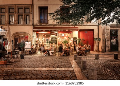 LYON, FRANCE - August 21, 2018: Colorful saint Jean district in old Lyon, the famous and typical old town of the city of Lyon by night. People on the terrace of typical restaurant.